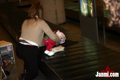 Mamá cambiando panñales en la cinta de las maletas del aeropuerto